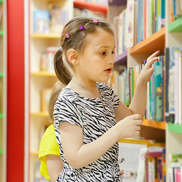 Little girl with a zebra print dress picking out a book in an isle of the library