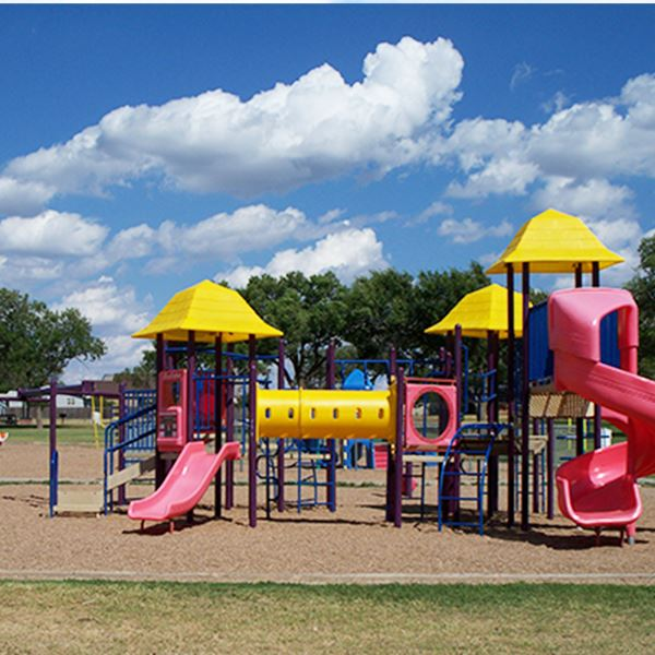 Playground equipment with yellow awnings and pink slides